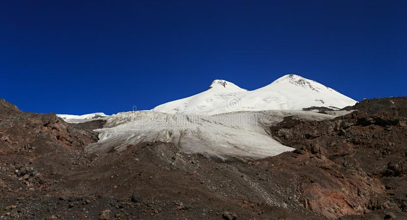 Panoramic view of the southern slope of Mount Elbrus. And the Small Azau Glacier of the Caucasus Mountains in Russia. Snow-covered mountain two peaks stock image