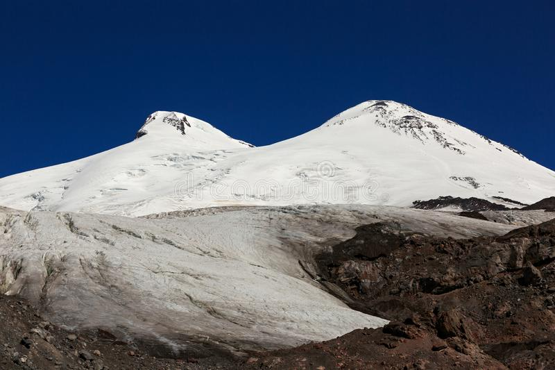 Panoramic view of the southern slope of Mount Elbrus. And the Small Azau Glacier of the Caucasus Mountains in Russia. Snow-covered mountain two peaks royalty free stock photography