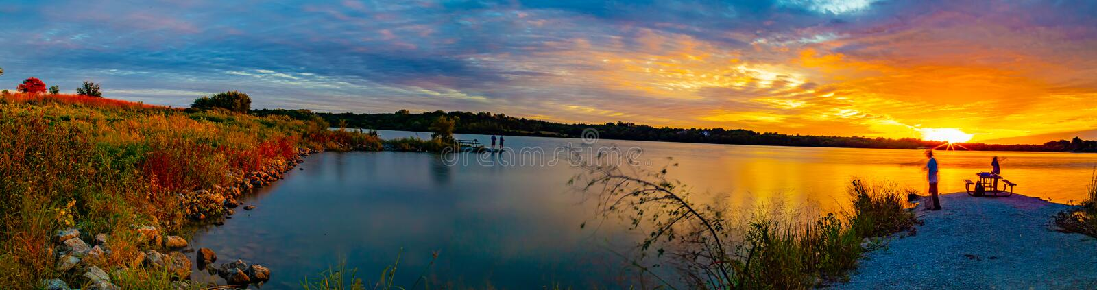 Panoramic view Sports Fishermen at Sunset early fall with beautiful skyline over Ed Zorinsky lake Omaha Nebraska. Water reflection. Sports Fishermen Sunset early stock image