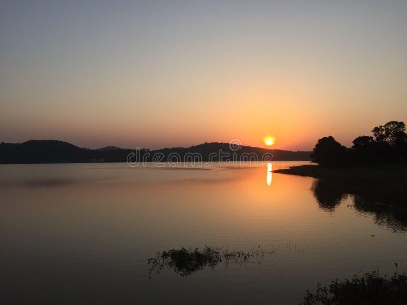 Sunset at Sunabeda, Koraput, India. Panoramic view of the sun setting at the horizon over a water body in Sunabeda, Koraput, India stock photos