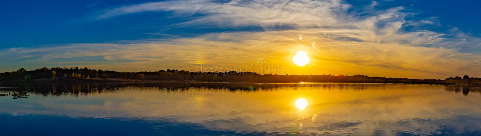 Panoramic view of sunset with beautiful skyline over lake Zorinsky Omaha Nebraska. Reflections of the round sun outline and surrounding beautiful cloud and stock images