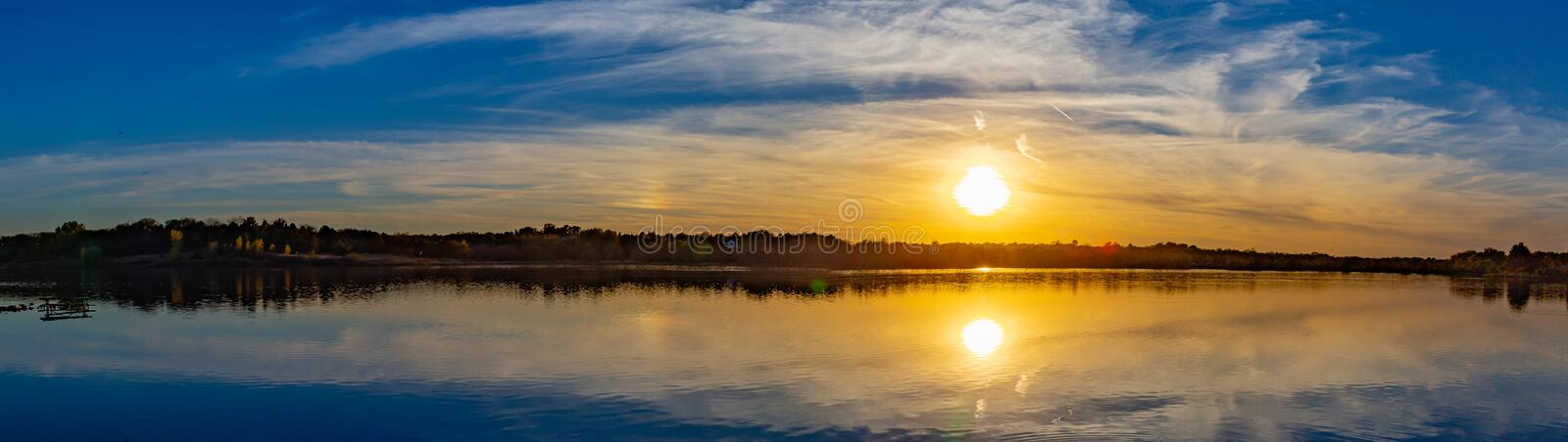 Panoramic view of sunset with beautiful skyline over lake Zorinsky Omaha Nebraska. There is reflection of the sun, skyline and the surrounding forest with fall royalty free stock photo
