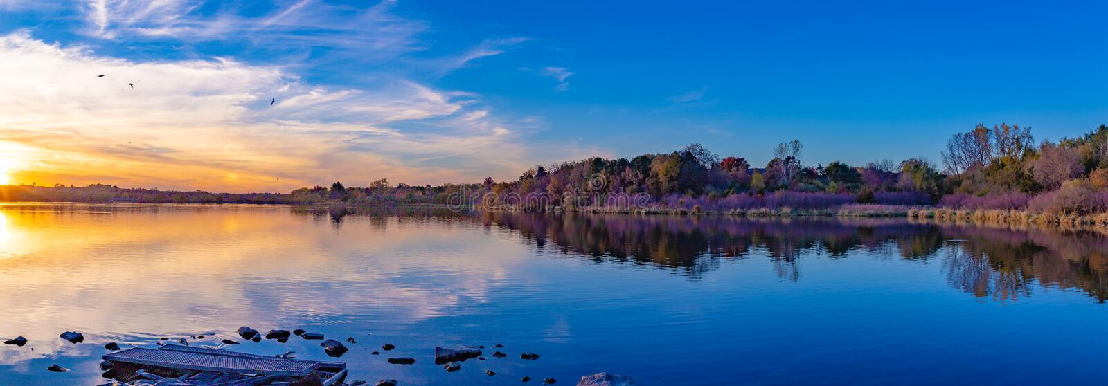 Panoramic view of sunset with beautiful skyline over lake Zorinsky Omaha Nebraska. There is reflection of the sun, skyline and the surrounding forest with fall stock photos