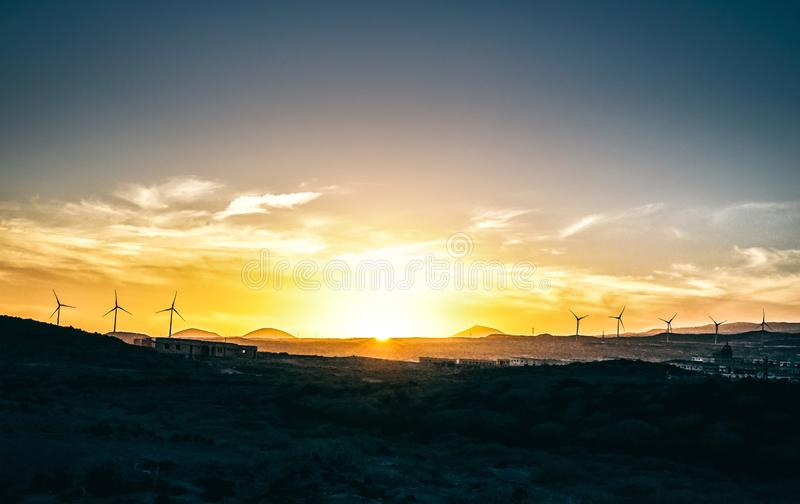 Panoramic view of a sunset over hills with mountains and wind turbines in the background - Vignette edit in the sky royalty free stock image