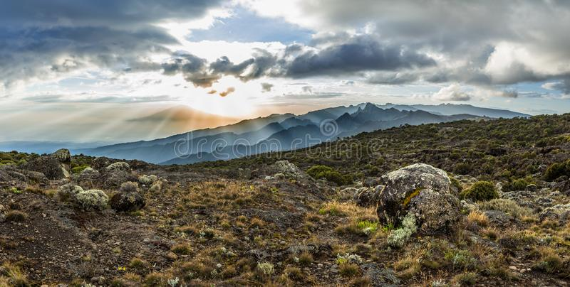 Panoramic view of sunset over Mount Meru in Tanzania taken from the Shira Cave camp on the Machame route of Kilimanjaro. Sunrays burst through the dramatic stock photos