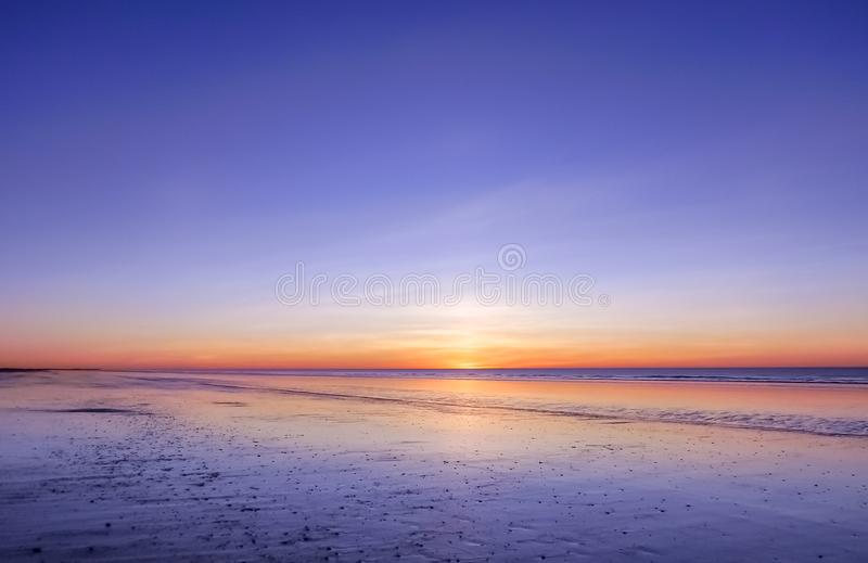 Panoramic view of sunset over ocean. Nothing but sky, clouds and water. Beautiful serene scene royalty free stock image