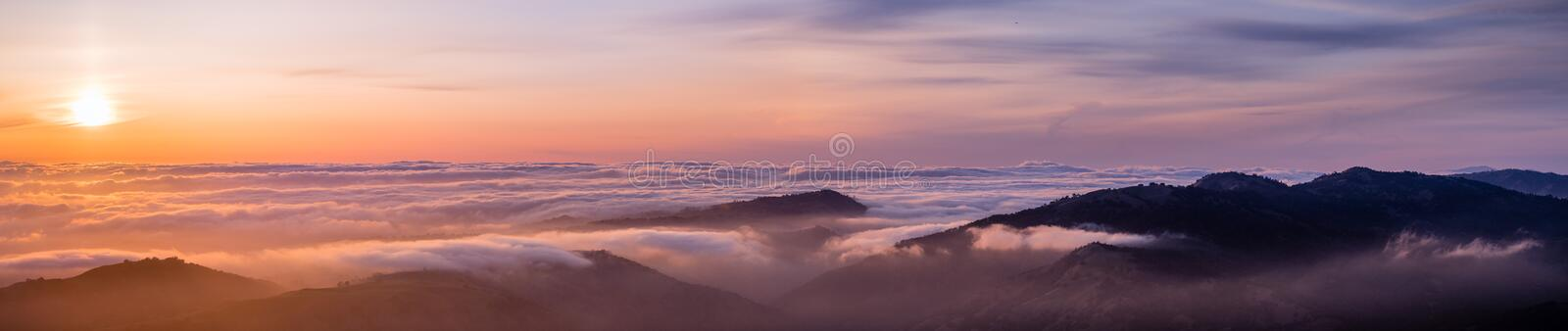 Panoramic view of a sunset over a sea of clouds covering south San Francisco bay area; mountain ridges in the foreground; view stock photography