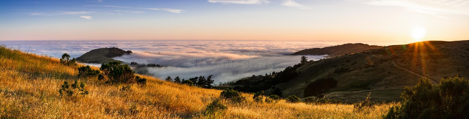 Panoramic view at sunset of valley covered in a sea of clouds in the Santa Cruz mountains, San Francisco bay area, California royalty free stock photo