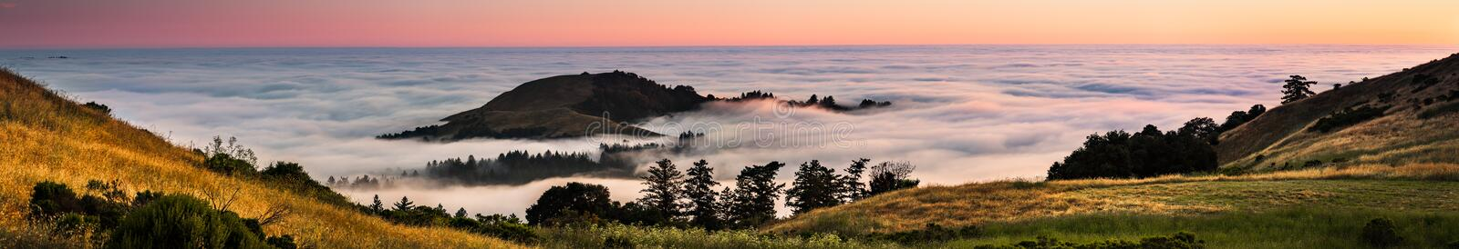 Panoramic view at sunset of valley covered in a sea of clouds in the Santa Cruz mountains, San Francisco bay area, California stock photo
