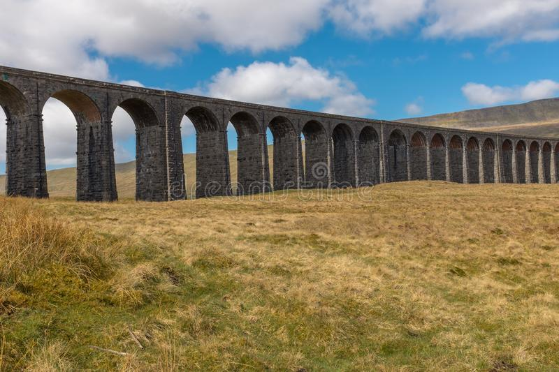 A panoramic view of the sweeping majestic Ribblehead Viaduct stands tall above the Ribble Valley, Yorkshire, England carrying the royalty free stock photos