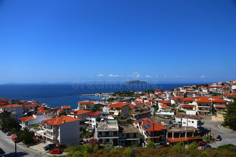 Panoramic view of the terracotta roofs of the city of Greece and the harbor. In the distance an island and a horizon line. Panoramic view of the terracotta stock photography