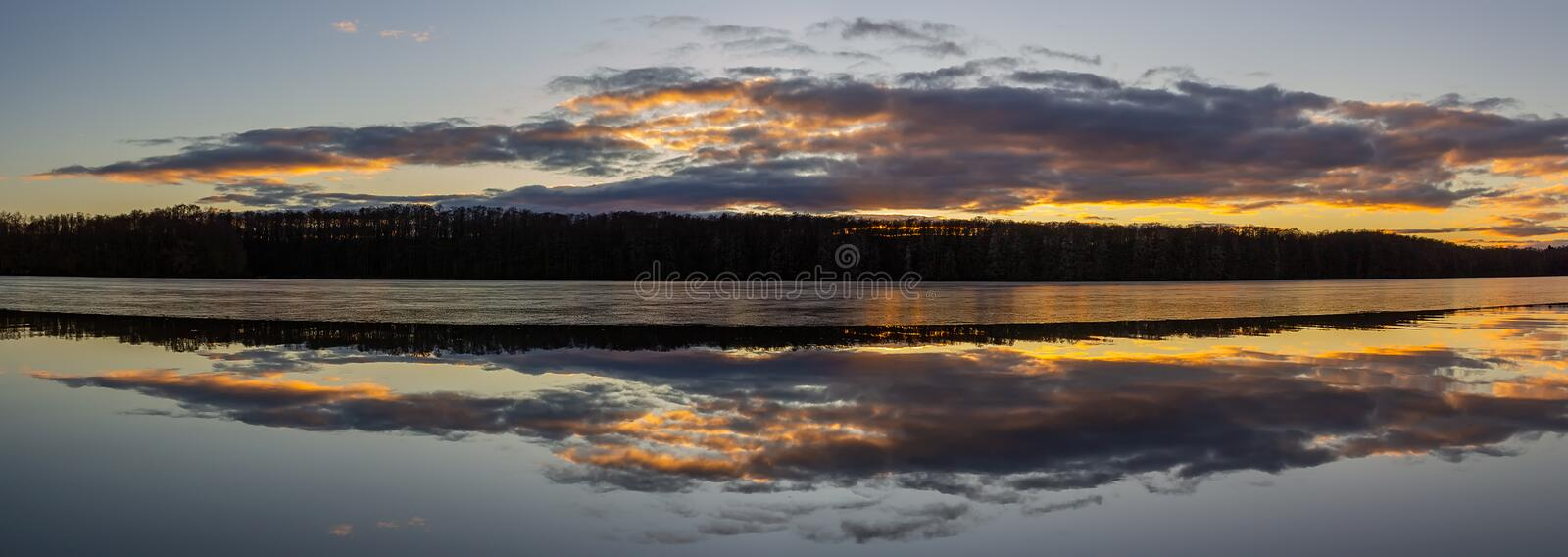 Panoramic view to icy pond  with trees at sunset. Czech landscape stock images