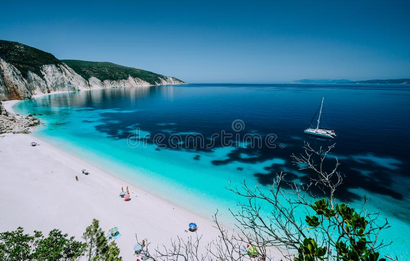 Panoramic view to remote beach wiht lonely white catamaran yacht drift in clear blue Caribbean like sea water. Tourists stock photography