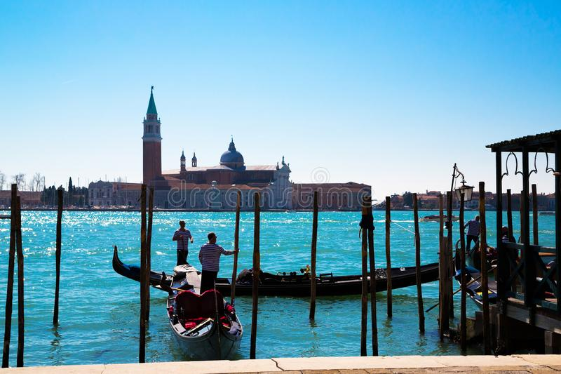 A panoramic view to the Venice lagoon, San Giorgio Maggiore island, to gondolas with tourists and gondolier moving to the San stock photos