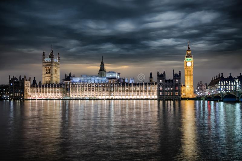 Panoramic view to the Westminster Palace, the Parliament of Great Britain and Big Ben clocktower by night. With bad weather storm clouds approaching stock photo