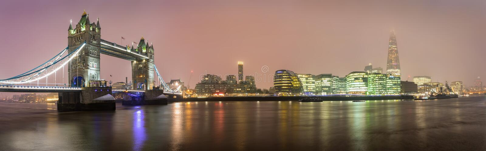 Panoramic view from the Tower Bridge to the London Bridge on a foggy winter night stock photography