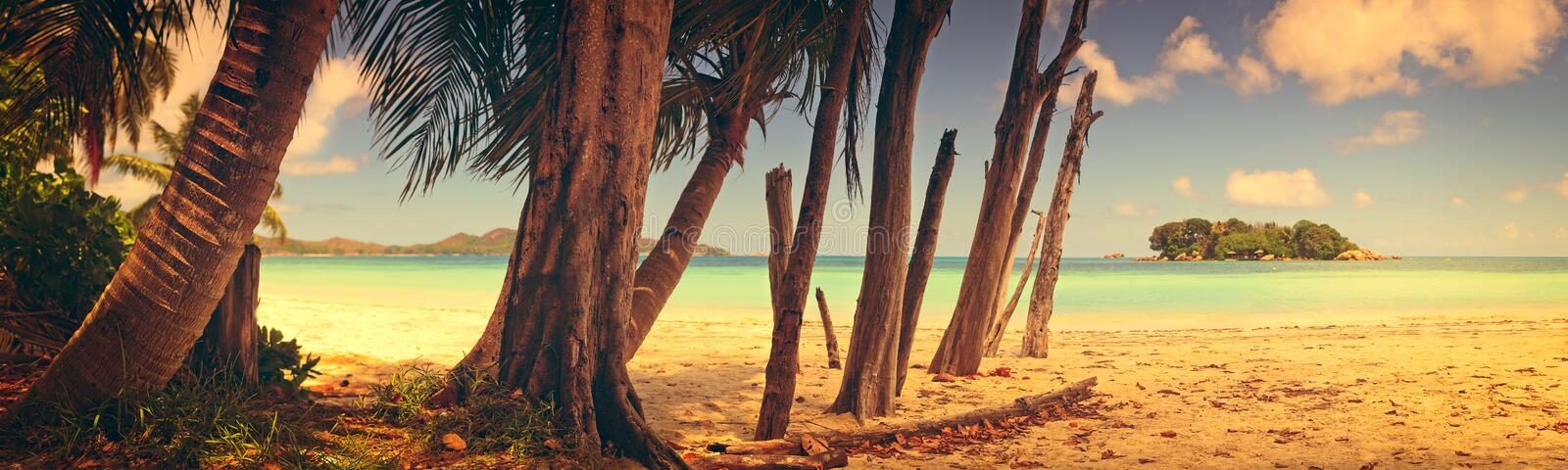 Panoramic view of a tropical beach at dawn. Praslin island, Seychelles, Indian Ocean vintage style stock images
