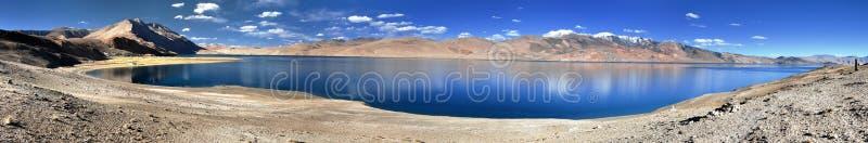 Panoramic view of Tso Moriri lake. Korzok village and mounts Chamser Kangri and Lungser Kangri - Rupshu valley - Ladakh - India - The lake is at an altitude of royalty free stock image