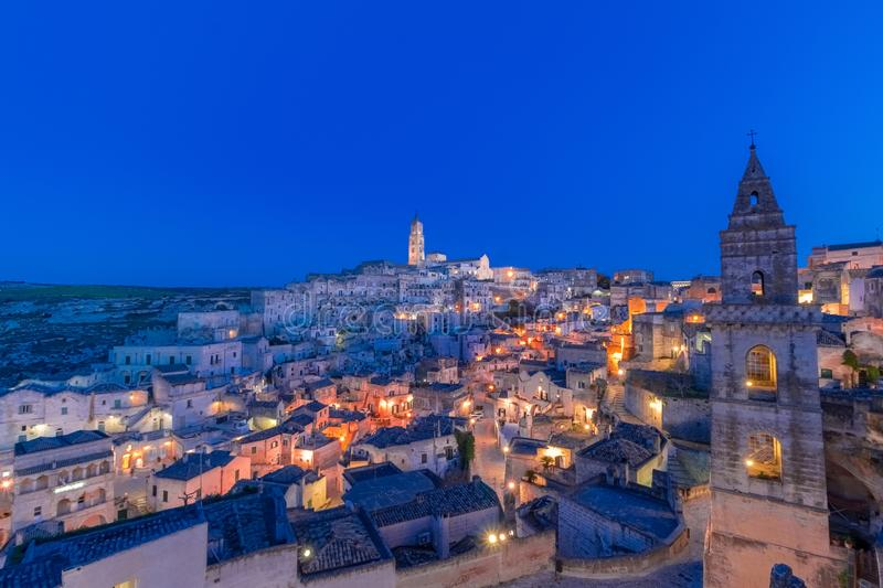 Panoramic view of typical stones Sassi di Matera and church of M. Atera under blue night sky. Basilicata, Italy with clouds movement in the sky stock photos