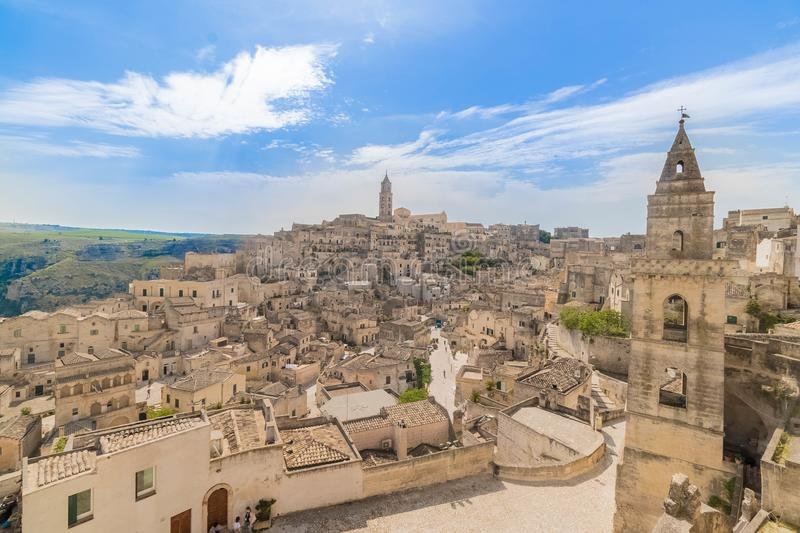 Panoramic view of typical stones Sassi di Matera and church of M. Atera under blue sky with clouds royalty free stock photography