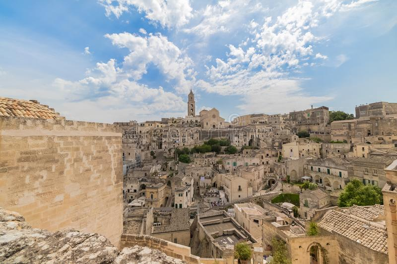 Panoramic view of typical stones Sassi di Matera and church of M. Atera under blue sky with clouds stock photography