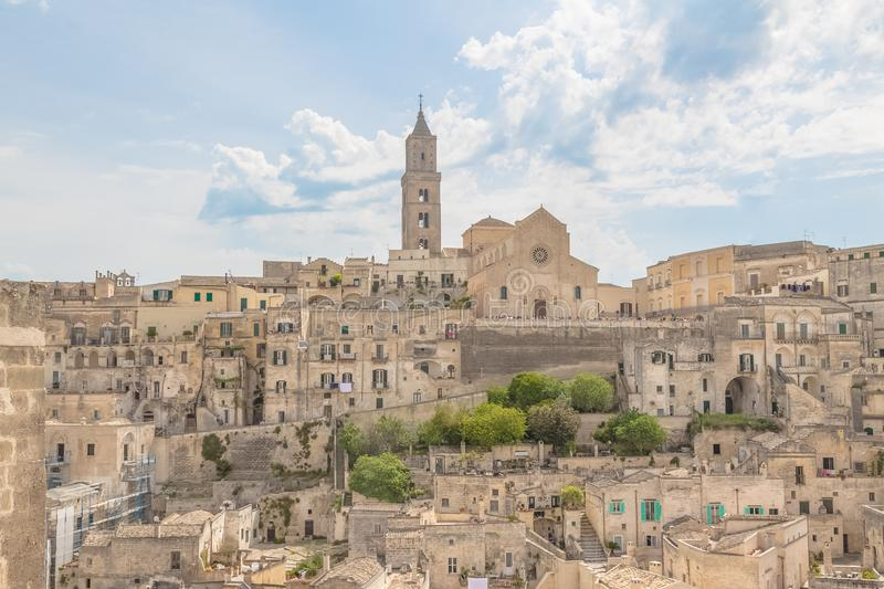 Panoramic view of typical stones Sassi di Matera and church of M. Atera under blue sky with clouds royalty free stock images