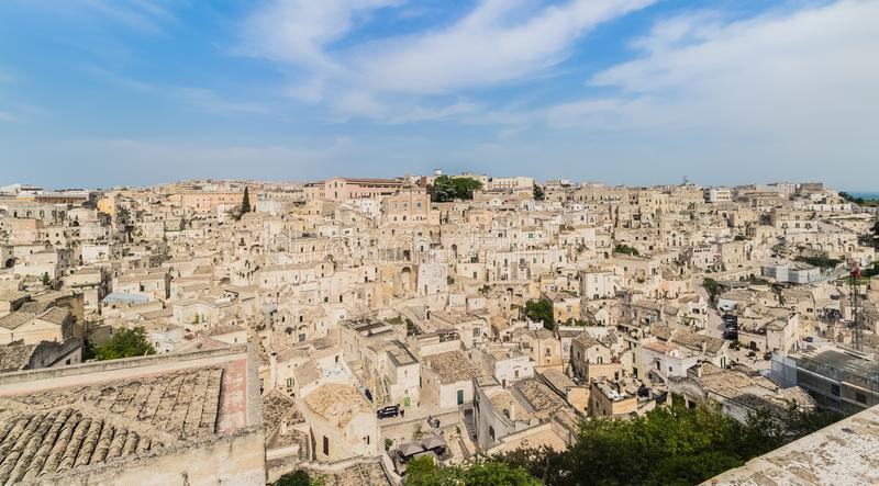 Panoramic view of typical stones Sassi di Matera and church of M. Atera under blue sky with clouds royalty free stock photo