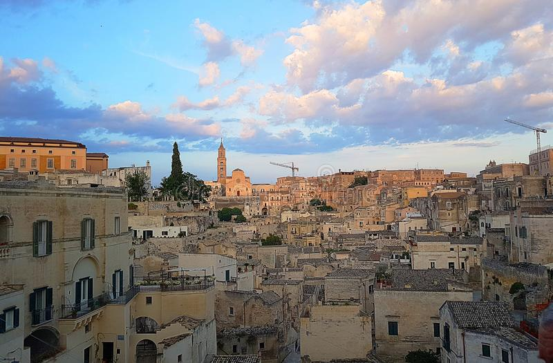 Panoramic view of typical stones Sassi di Matera and church of. Matera UNESCO European Capital of Culture 2019 under blue sky white clouds, Basilicata, Italy stock image