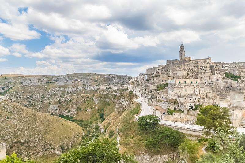 Panoramic view of typical stones Sassi di Matera and church of. Matera UNESCO European Capital of Culture 2019 under blue sky white clouds, Basilicata, Italy royalty free stock image
