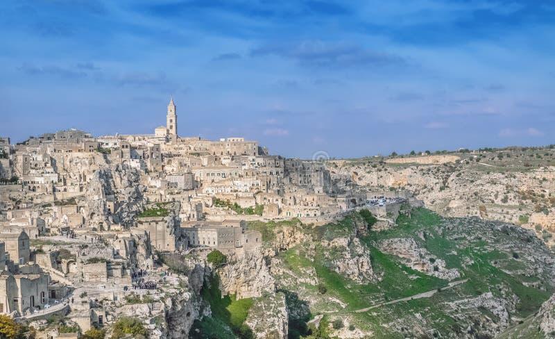 Panoramic view of typical stones (Sassi di Matera) and church near gravina of Matera UNESCO European Capital of Culture 2019 under. Blue sky. Basilicata, Italy royalty free stock photos