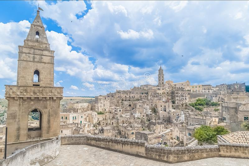 Panoramic view of typical stones Sassi di Matera and church of. Matera UNESCO European Capital of Culture 2019 under blue sky white clouds, Basilicata, Italy royalty free stock photo