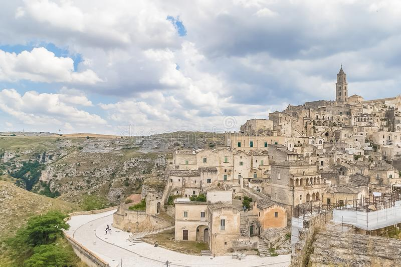 Panoramic view of typical stones Sassi di Matera and church of. Matera UNESCO European Capital of Culture 2019 under blue sky white clouds, Basilicata, Italy stock photos