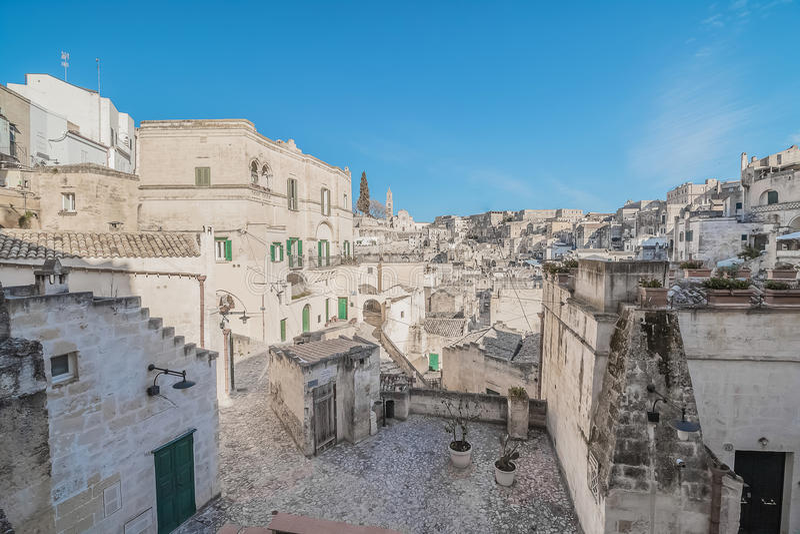 Panoramic view of typical stones Sassi di Matera near gravina of Matera UNESCO European Capital of Culture 2019 on blue sky. Basilicata, Italy royalty free stock photo