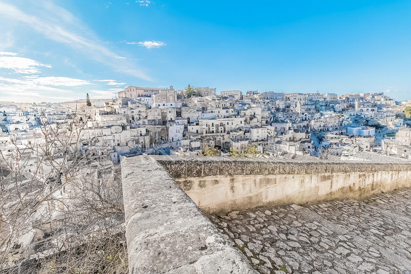 Panoramic view of typical stones Sassi di Matera near gravina of Matera UNESCO European Capital of Culture 2019 on blue sky. Basilicata, Italy royalty free stock images