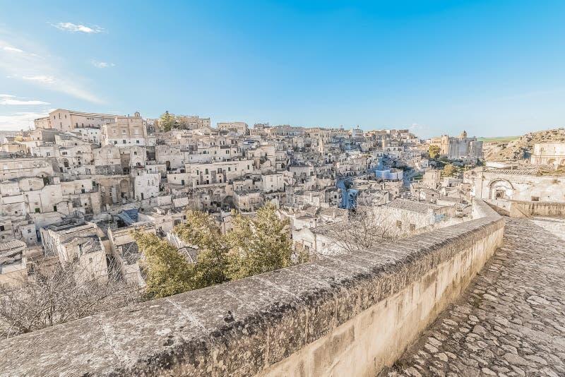 Panoramic view of typical stones Sassi di Matera near gravina of Matera UNESCO European Capital of Culture 2019 on blue sky. Basilicata, Italy stock image