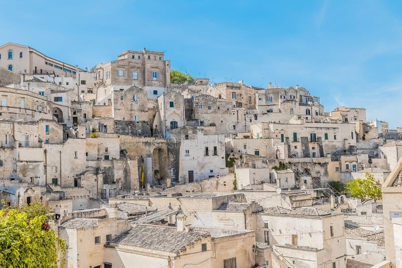 Panoramic view of typical stones Sassi di Matera near gravina of Matera UNESCO European Capital of Culture 2019 on blue sky. Basilicata, Italy royalty free stock photography