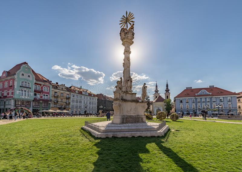 Panoramic View of Union Square in Timisoara and Statue of Holy Trinity backlit from the sun. Statue of Holy Trinity in Union Square in Timisoara, Romania , the stock photo