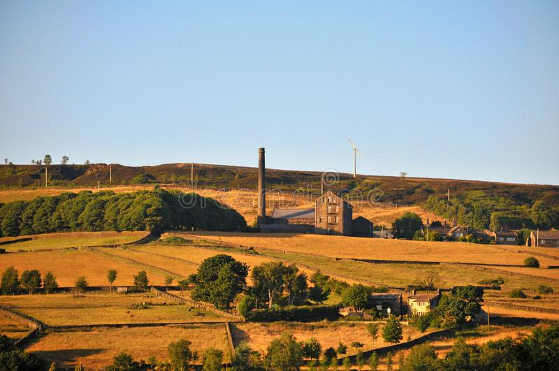 A panoramic view of the village of old town near hebden bridge in west yorkshire with summer sunshine on farms and old mill. Buildings with midgley moor at the stock image