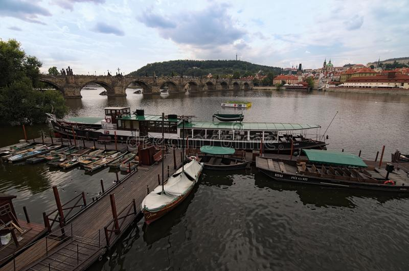 Panoramic view of Vltava river with Charles Bridge and many historical buildings. Small pier with different boats for tourist trip royalty free stock photography