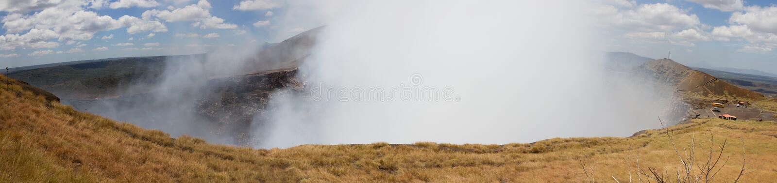 Panoramic view of Volcano Masaya. The view over the crater of the active Masaya volcano in Nicaragua. With smoke billowing out of the crater and over the cars stock photos