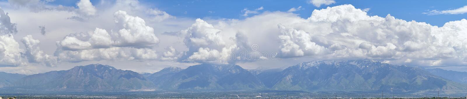 Panoramic view of Wasatch Front Rocky Mountains, Great Salt Lake Valley in early spring with melting snow and Cloudscape. royalty free stock photos