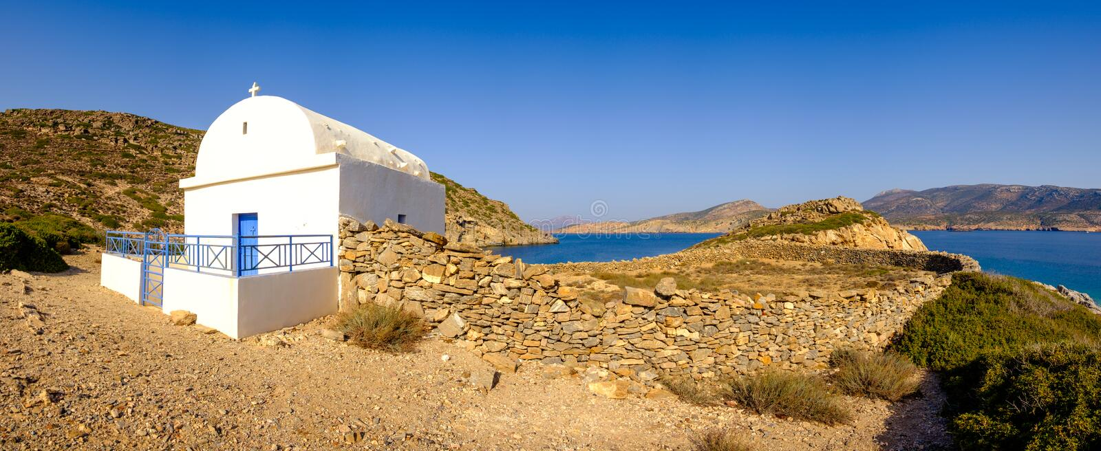 Panoramic view of white chapel at beautiful ocean coastline, Greece royalty free stock photos