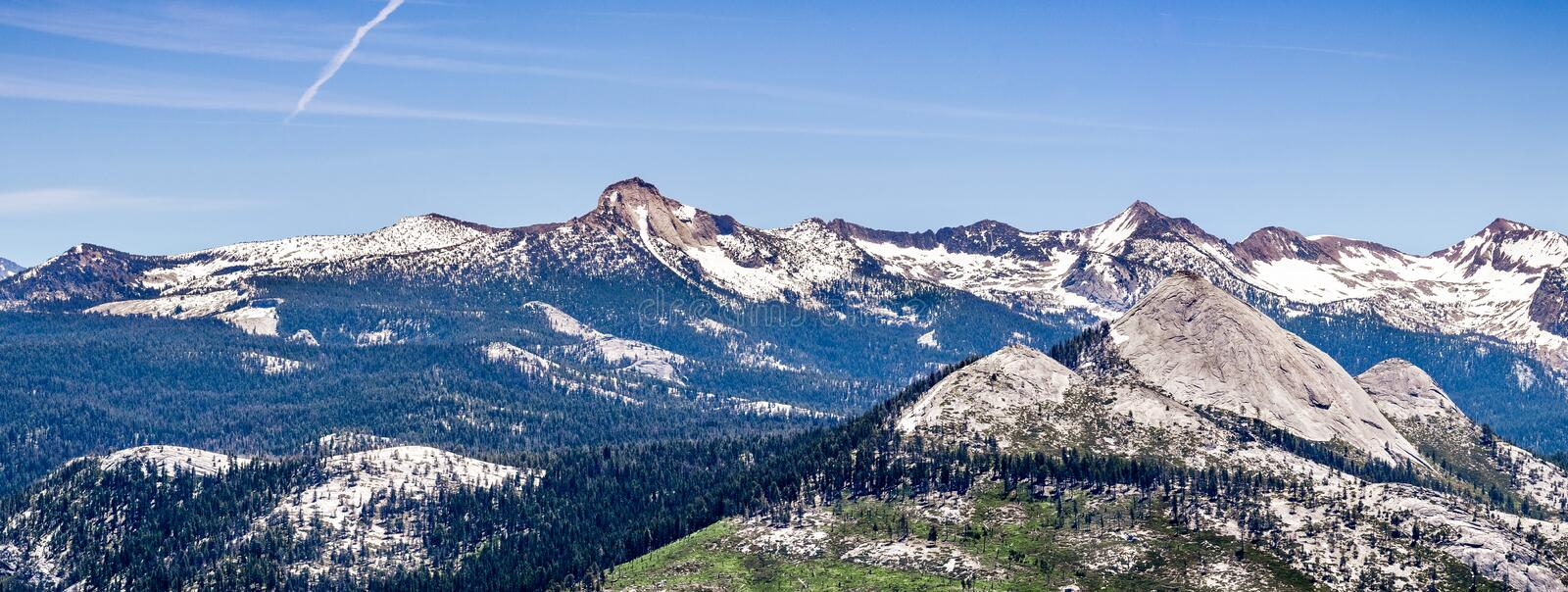 Panoramic view of wilderness areas in Yosemite National Park with mountain peaks covered in snow; Sierra Nevada mountains,. California royalty free stock image