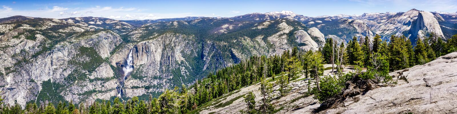Panoramic view in Yosemite National Park with Yosemite falls on the right and Half Dome on the left; snow covered peaks visible in. The background; Sierra royalty free stock photography