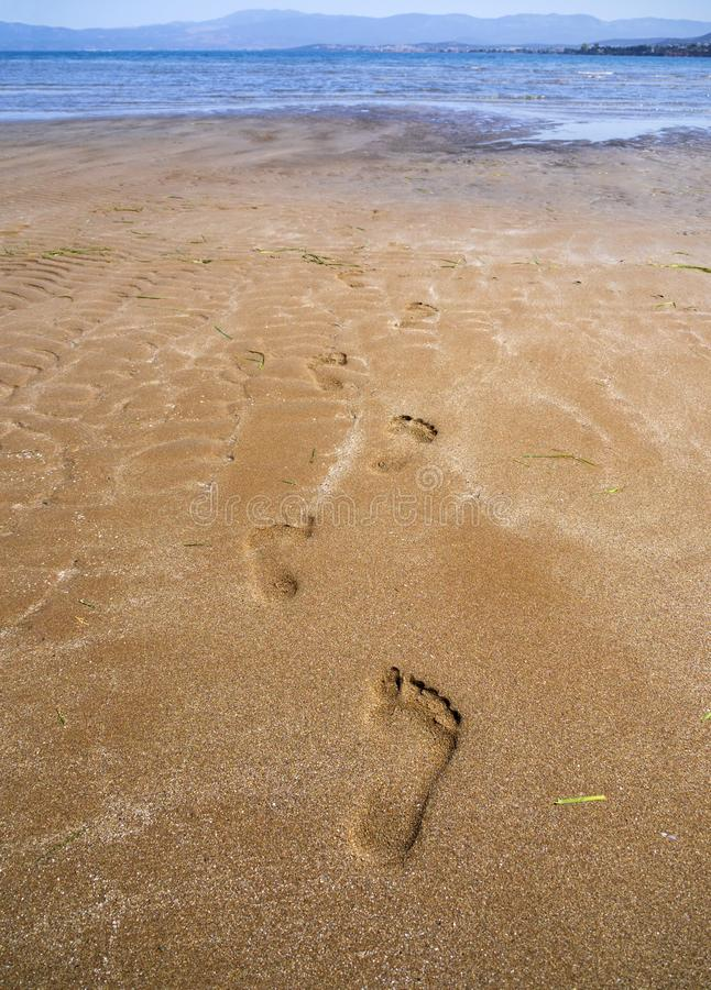 Panoramic views of the sandy beach, the mountains and footprints in the sand at low tide on Liani Ammos beach in Halkida, Greece o. N a Sunny summer  day the stock image