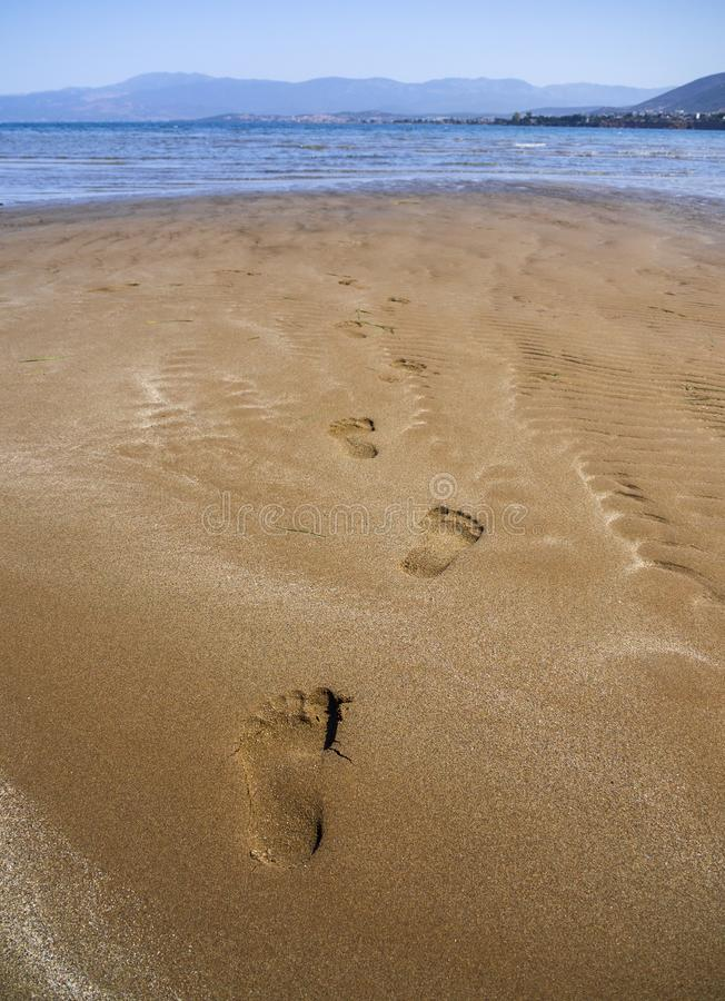 Panoramic views of the sandy beach, the mountains and footprints in the sand at low tide on Liani Ammos beach in Halkida, Greece o. N a Sunny summer day the royalty free stock photography