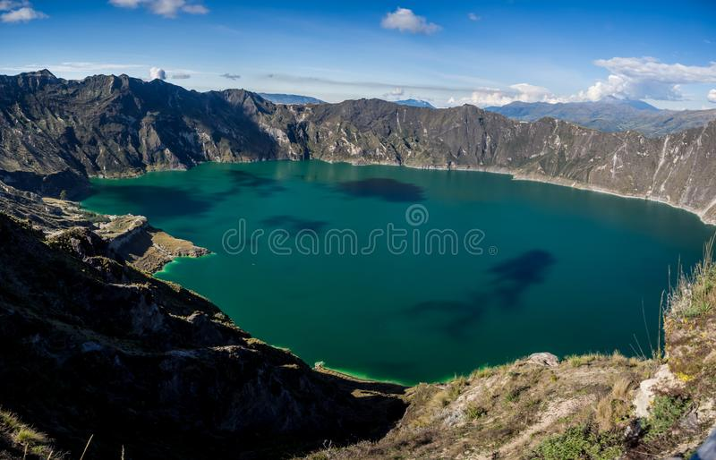 Panoramic of the volcano lake of Quilotoa, Ecuador. With a little kayak inside stock photo