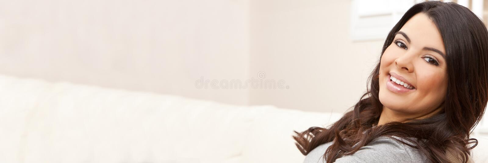 Happy Hispanic Woman Sitting on a Sofa at Home Panorama stock images