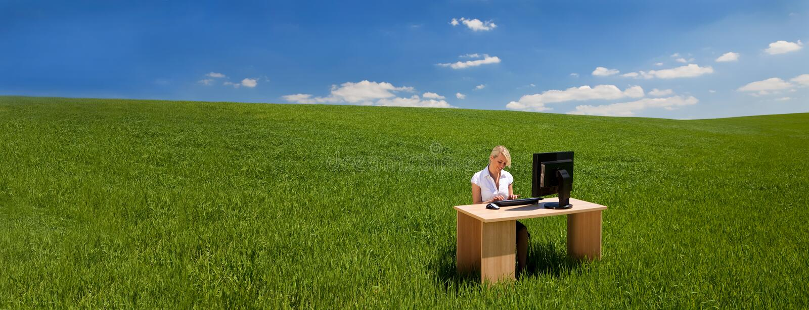 Panorama businesswoman using computer at a desk in green field banner royalty free stock photography
