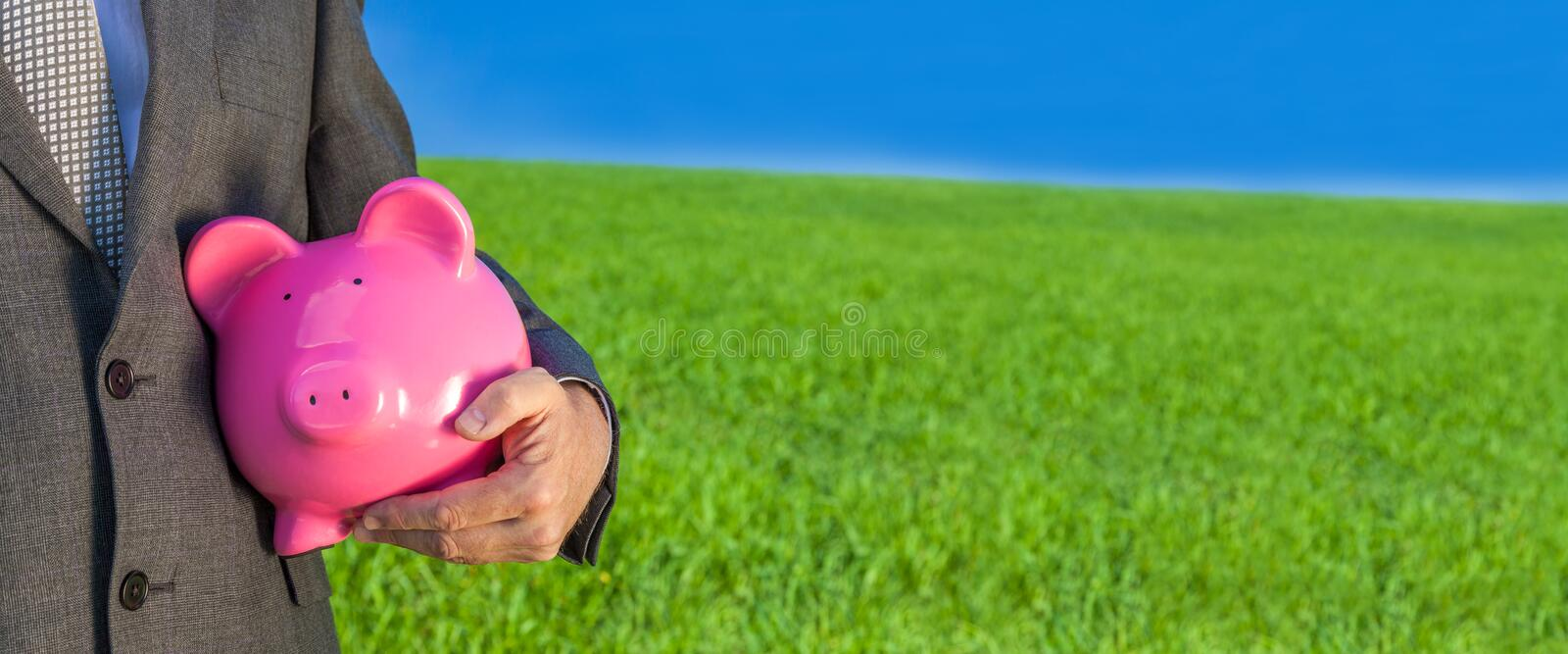 Panoramic Man Businessman Holding Piggy Bank in Field Banner stock photo